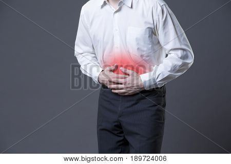 Man with abdominal pain stomach ache on gray background with red dot