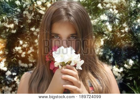 the girl in the Park among the flowers smelling flowers