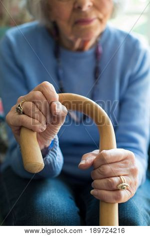 Close Up Of Senior Woman Sitting In Chair Holding Walking Cane