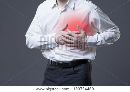 Heart attack man with chest pain on gray background with red dot