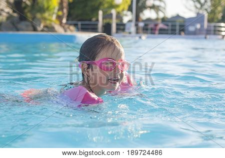 Little girl enjoying the summer at swiming pool. She wears armbands and goggles