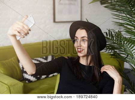 Attractive Caucasian girl holding camera and shooting himself sitting in modern interior co-working while waiting her friends. Bright brunette woman is taking fun while making selfie by smart phone