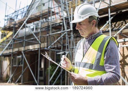 Building Inspector Looking At House Renovation Project