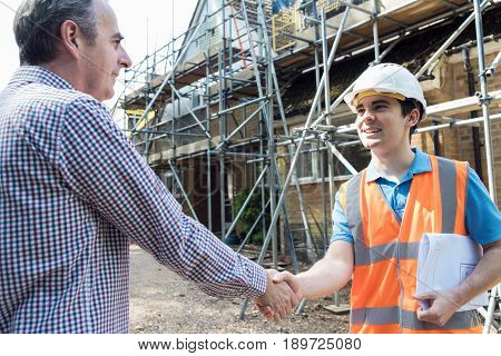 Customer On Site Shaking Hands With Builder