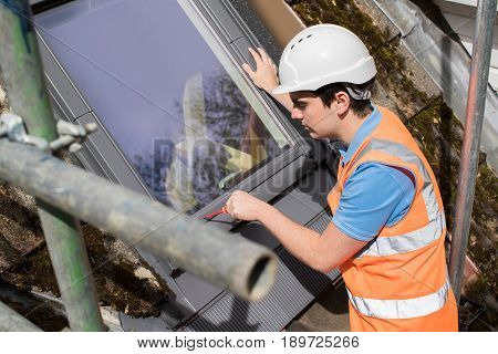 Construction Worker On Roof Installing Replacement Window