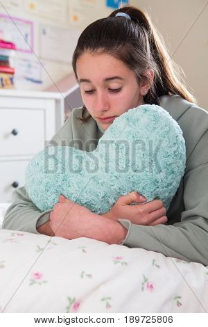 Young Girl Lying On Bed Hugging Heart Shaped Cushion