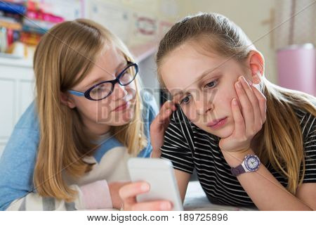 Pre Teen Girl With Friend Being Bullied By Text Message