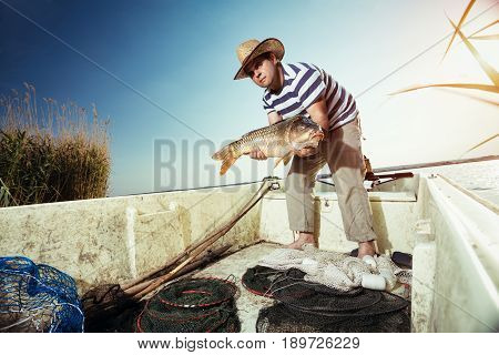 fisherman holding a big carp on the boat