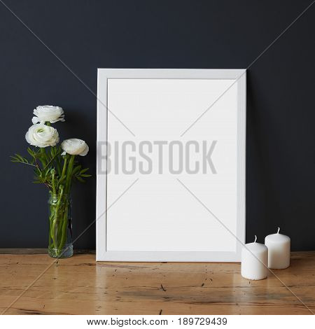 Empty white wooden picture frame on the table art print mock-up Scandinavian interior background. White poster canvas on grey wall with clean blank for design advertising and other content picture