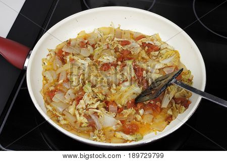 Mixed white onions napa cabbage red tomatoes and garlic cooking in a saucepan. Savory vegetables to serve with dinner cooking in a pan on a stove.