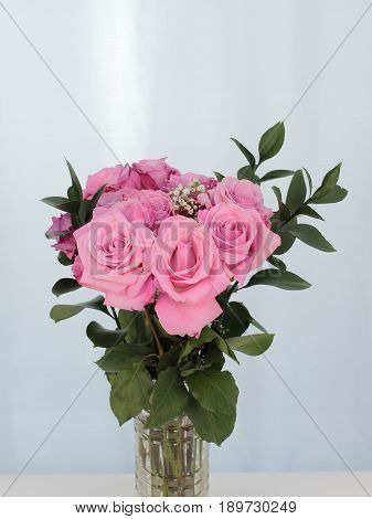 Vibrant pink rose flowers bunch in a cut-glass vase with a subtle background. Green leaves and baby's breath accent pink bouquet of roses in a clear glass vase.