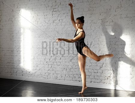 Young asian young woman dancing Contemporary in studio against white brick wall. Attractive female wearing in black bodusuit coached ballet plie for fun after hard working day. Body ballet concept