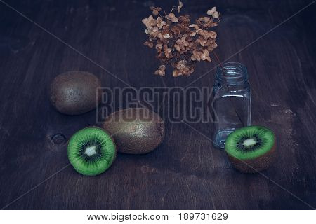 Kiwi on a wooden table with a sprig of dried flowers. Still life with kiwi.