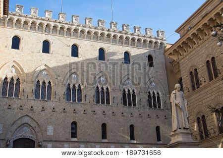 Italy Siena - December 26 2016: the view of facade detail of the 14th century building in Salimbeni square the world's oldest bank established in 1472 in Siena on December 26 2016 in Siena Tuscany Italy.