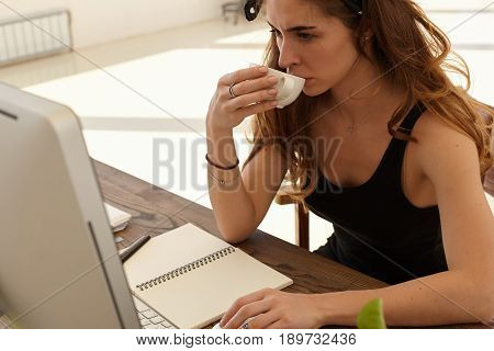Cropped shot of a successful young female entrepreneur thinking over new business startup working with documents in freelance. Confident woman drinking coffee while working via PC computer at home
