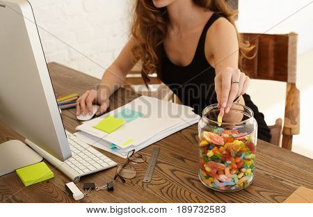 Cropped image of young stressed woman eating sweets at workplace in office. The girl takes candy from big glass jar with lollipops standing on a desktop. Stress and junk food concept