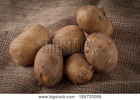 Raw potatoes lying on a jute bag