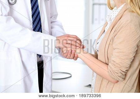 Hand of doctor reassuring her female patient. Medical ethics and trust concept.