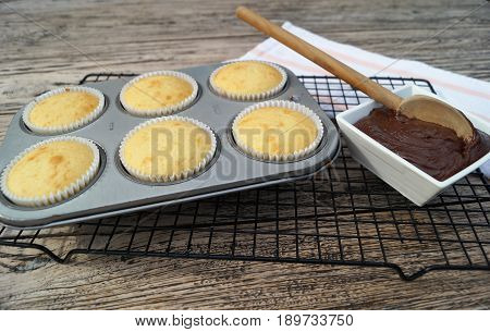 Decorating Homemade Cupcakes. An authentic kitchen scene of baking at home with freshly baked cupcakes waiting to be frosted