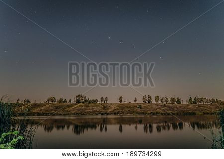 Starry night over the lake. Big dipper in the night sky.