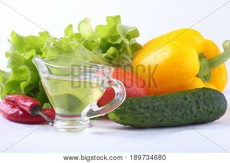 Assorted vegetables, fresh bell pepper, tomato, chilli pepper, cucumber, olive oil and lettuce isolated on white background. Selective focus