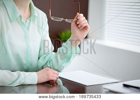 Business woman hands in a green blouse sitting at the desk in the office and holding glasses, the right window . She is thinking about the business problems, the successes, the concept