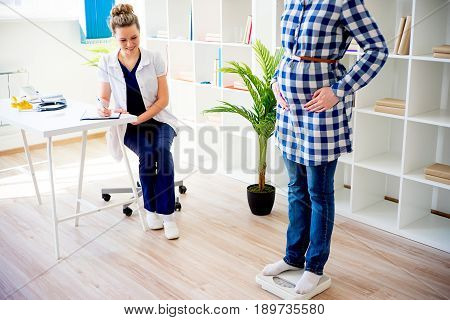 Pregnant woman checking her weight on a scale