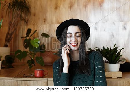 Portrait of a charming female in love of the European appearance dreamily closed eyes talking by cell phone with her boyfriend sitting in modern cafe. Relationship happiness and love concept