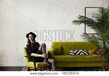 Stylish Caucasian fashion designer with charming smile dressed in black sitting in green colored armchair resting in modern interior in Scandinavian style at home. Empty space wall for your content
