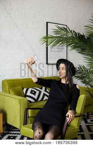 Vertical portrait of handsome Caucasian girl taking selfie siiting in modern interior copy space for text. Fashionable dressed in black pretty girl resting in green armchair against sofa palm plant