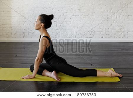 Profile portrait of a Mixed race Chinese and Caucasian young woman doing One Legged King Pigeon Pose Single Pigeon. Attractive asian young woman practicing yoga pose Eka Pada Radjakapotasana