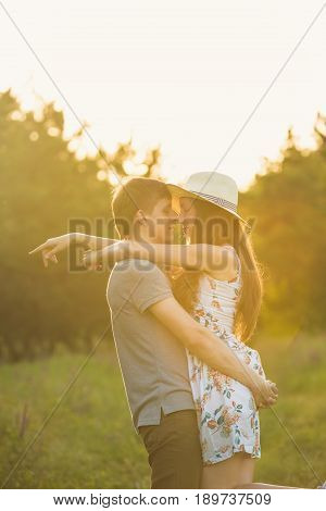 A guy is picking up a girl in a cowboy hat in the forest against a sunset background