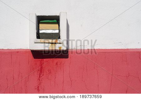 Drain hole in the wall. Square hole on a white red wall. Wastewater from a flat roof