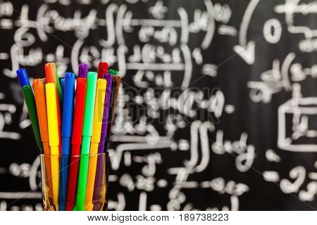 Back to school background with colorful felt pens and blurred math formulas written by white chalk on the black school chalkboard
