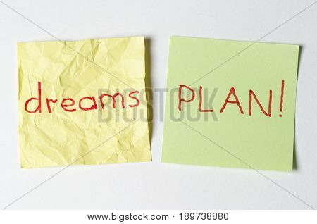 Crumpled dream word and plan word over white background