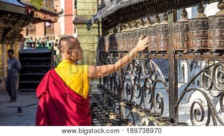 Swayambunath, Nepal - October 20, 2014: A buddhist monk spinning prayer wheel at Swayambunath temple