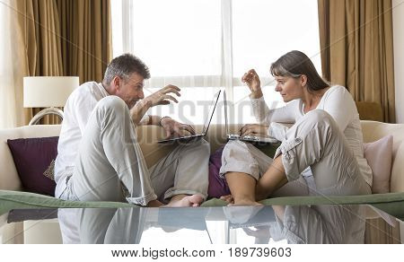 middle aged couple sitting on a sofa both working with their computers