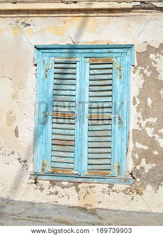 old blue wooden window with rust - abandoned house Hydra island Greece