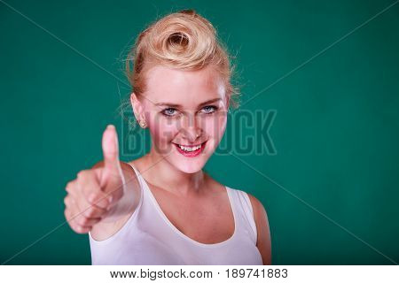 Symbols gestures concept. Smiling young woman with pinup hair making thumb up gesture. Studio shot on green background