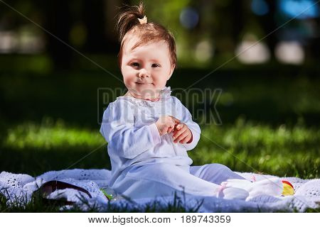Baby girl in summer dress sitting in the green meadow in the city park. Cute little girl in the beautiful white clothing. Horizontal photo. Sunshiny summer day. Concept of the happy children.