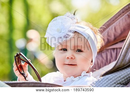 Close-up of the funny baby girl sitting in the stroller and holds sunglasses. Cute little girl in the white dress and with bow on her head. Sunshiny summer day in the city park. Concept of the happy babies.