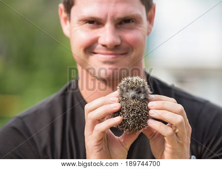 Young man with cute and funny hedgehog baby.