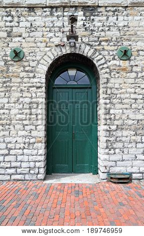 A green wooden door in a white stone building
