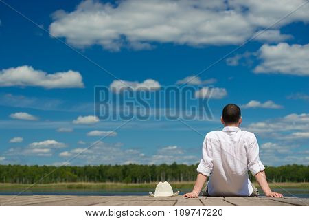 the man took off his hat and sat looking at beautiful lake