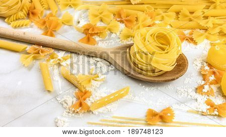 A closeup of various types of pasta, including pappardelle, farfalle, penne, and fusilli, on a white marble table with flour and a place for text