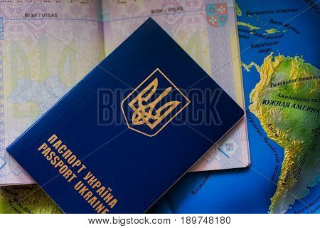 A closed foreign passport of Ukraine lies on an open passport and on the world map. Free entry to Europe for Ukrainians. Passports for departure to Europe without visas. Visa-free regime for Ukraine.