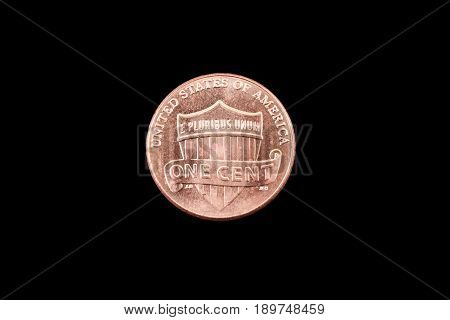 A close up image of an American one cent coin on a black background
