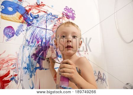 Portrait of cute adorable white Caucasian little boy playing and painting with paints on wall in bathroom having fun lifestyle childhood concept