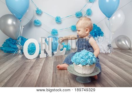 Portrait of cute adorable blond Caucasian baby boy with blue eyes in jeans overall celebrating his first birthday with gourmet cake holding letters one cake smash in studio