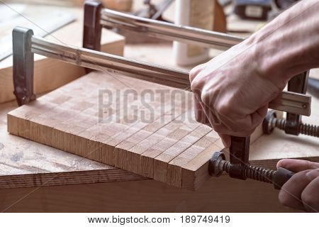 Joiner Fastens Clamps On A Wooden Surface For Better Gluing. Joinery Work On The Creation Of Furnitu